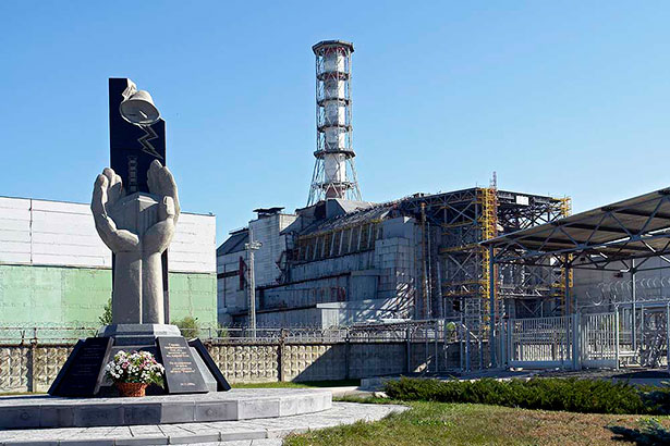 Ruine mit Mahnmal: REchts der Sarkophag über Reaktor 4, links ein Denkmal für die verstrahlten Arbeiter.