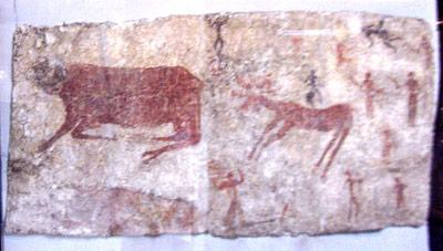 8.000 Jahre alte Wandmalerei eines Stieres, eines Hirschen und eines Mannes.