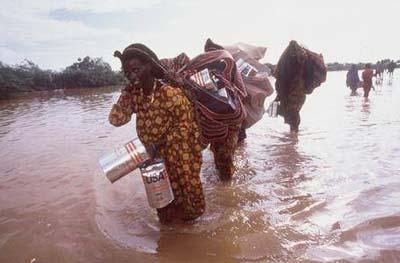Überschwemmung in Somalia. Flüchtlinge tragen ihre Habseligkeiten durchs Wasser.