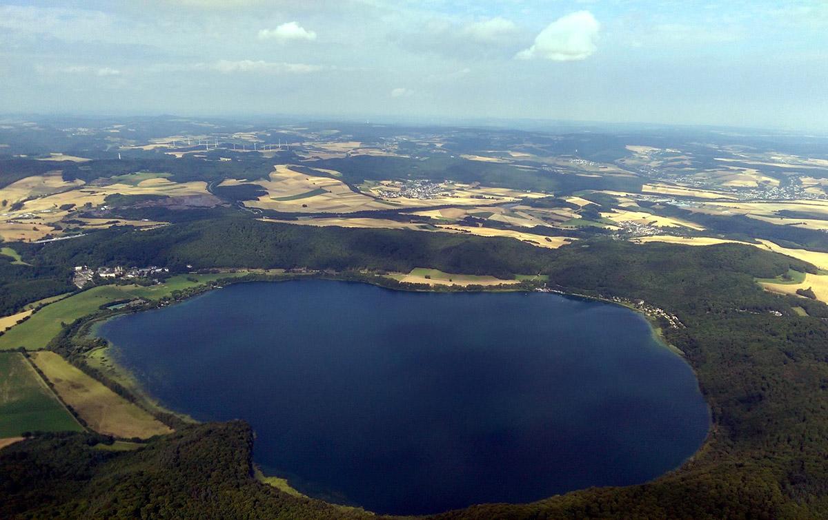 """<span class=""""img-caption"""">Blick auf den Laacher See – er ist ein Relikt des gewaltigen Vulkanausbruchs vor rund 12.900 Jahren in der Eifel.</span> <span class=""""img-copyright""""> Df1paw © <a href=""""http://creativecommons.org/licenses/by/4.0"""">CC-by-sa 4.0</a></span>"""