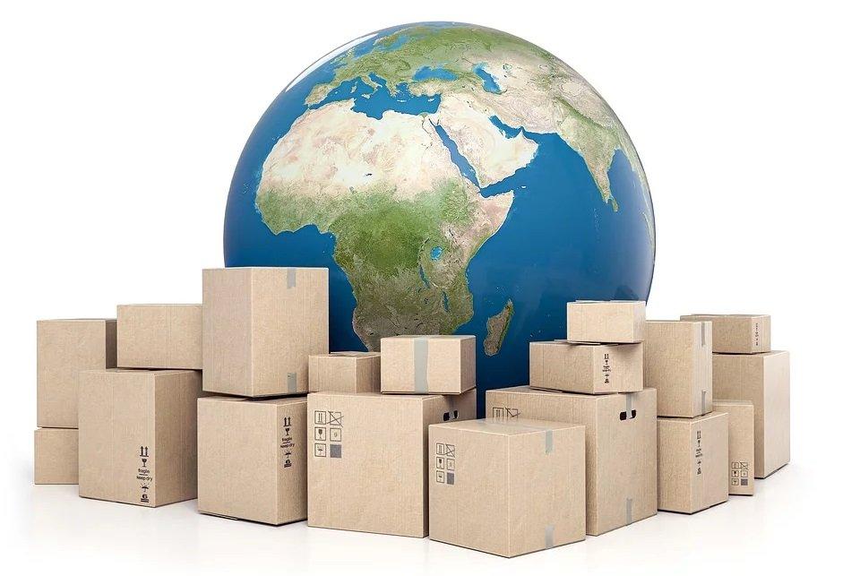 Viele Pakete stehen vor einer großen Weltkugel