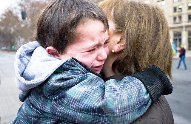 Weinender Junge in den Amen seiner Mutter