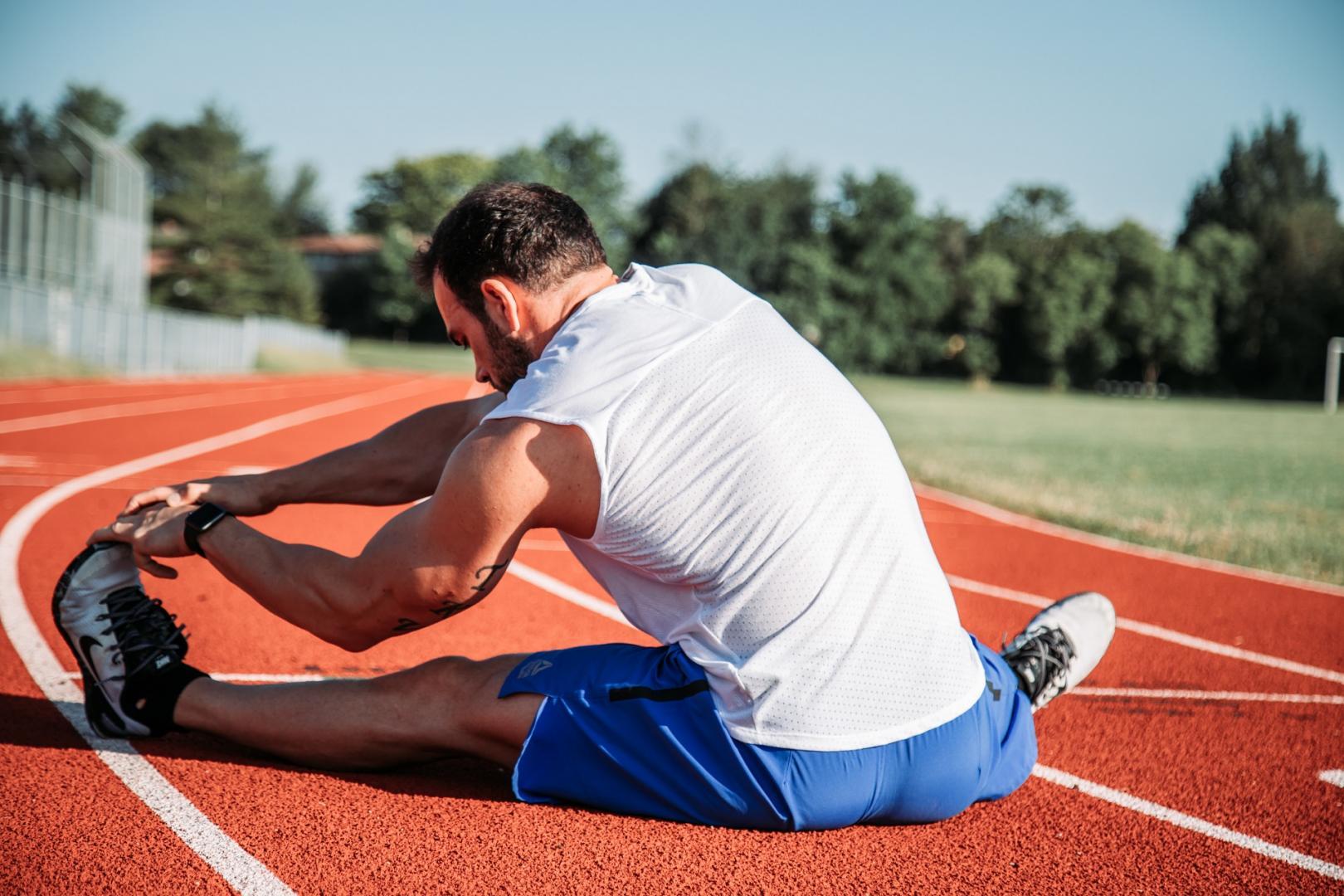 Männlicher Sportler bei Dehnübungen