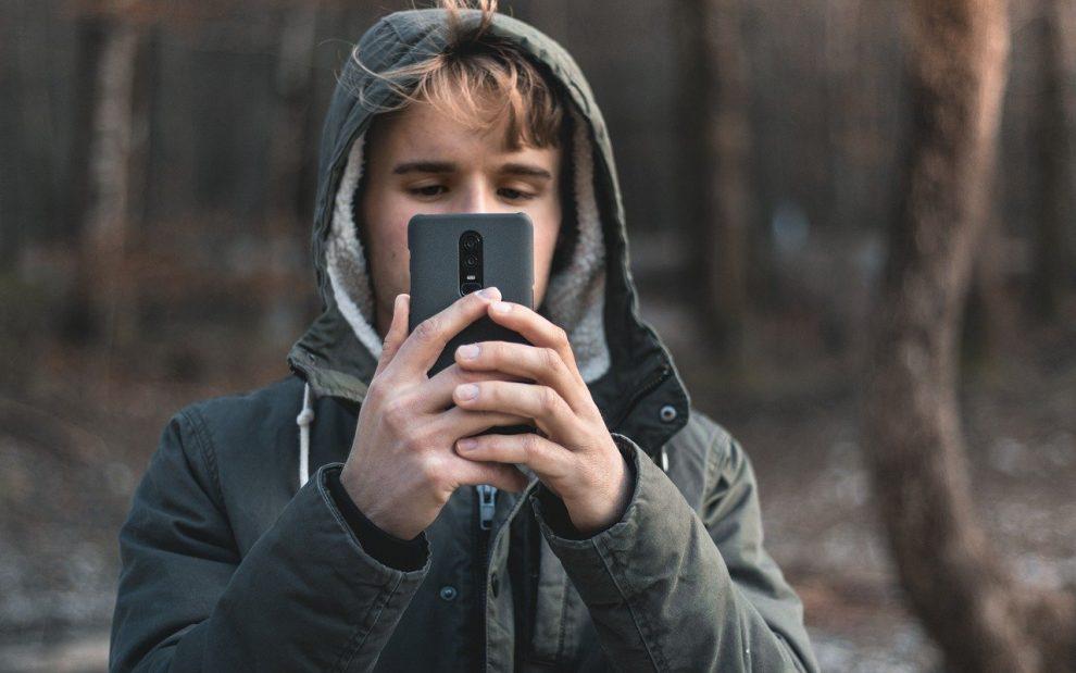 Junger Mann mit Smartphone vor dem Gesicht