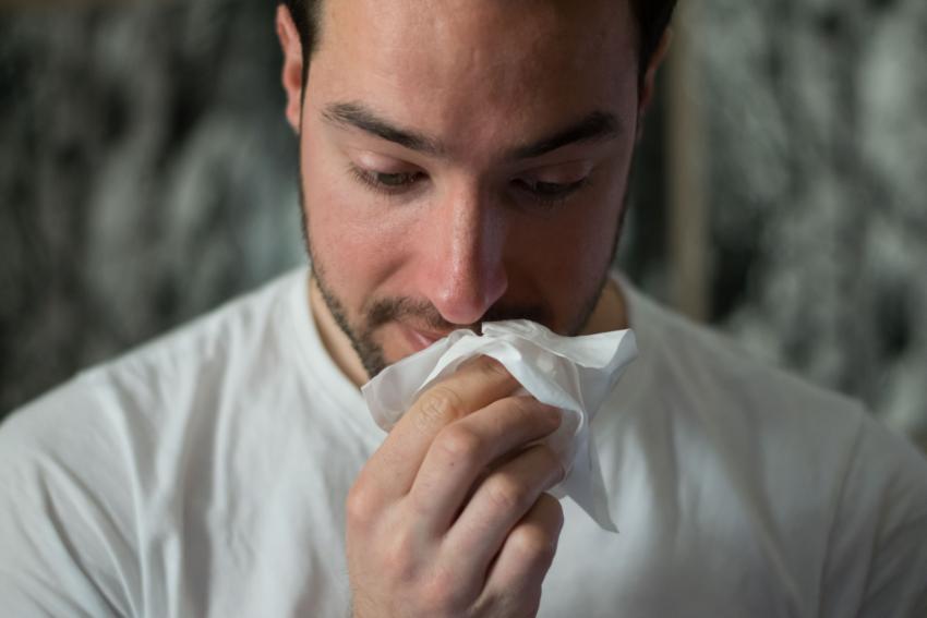 Mann beim Naseschnäuzen