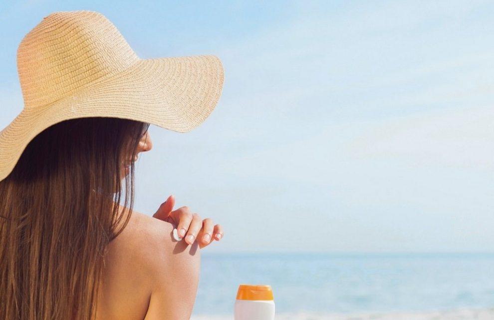 Brünette Frau beim Auftrage von Sonnencreme auf der Schulter