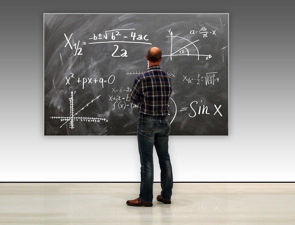 Mann vor Bilder einer Wandtafel mit mathematischen Formeln